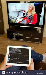 Female sat on couch watching TV whilst using Apple iPad 2 and TV Stock  Photo - Alamy