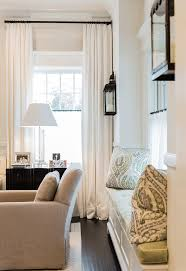 black lantern wall sconces window upholstered seating ivory curtains black curtain rods neutral colors off white ivory and blue traditional home