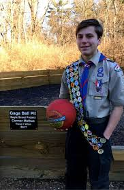 boy scout connor mathus of troop 7 holds a a ball in front of the ball