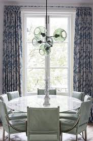 gorgeous dining room features a green glass pendant hanging over a round marble saarinen dining table lined with gray green leather dining chairs placed in