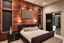 modern master bedroom with wood accent wall and contemporary furniture