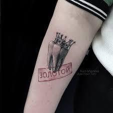 фото реалистичной татуировки на руке у девушки зуб в короне по