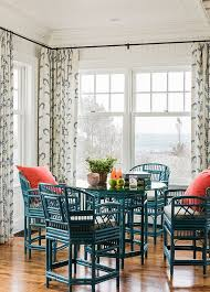 bright open coastal dining space featuring bold teal chairs and dining table