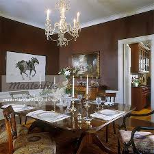 dark brown sponge paint white molding and trim artwork chinese horse in black and white formal place settings crystal chandelier regency style chairs