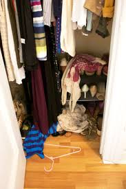 a small apartment s unorganized closet with messy shirts on the floor