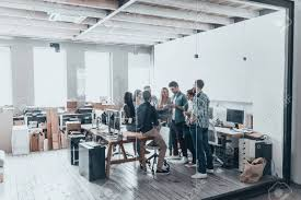 the creative office. Full Length Of Young Modern People In Smart Casual Wear Having A Meeting While Standing Behind The Glass Wall Creative Office