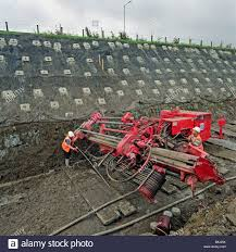 contractor using soil nailing techniques to create a rening wall for a railway cutting excavated through unle ground