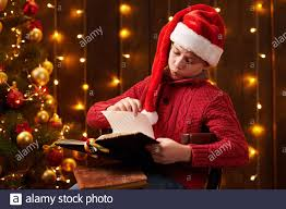 Holiday Indoor Lights Teen Boy Reading Book Sitting Indoor Near Decorated Xmas