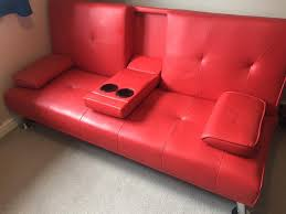 red faux leather sofa bed with armrest cup holders