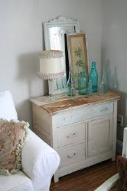 wooden vintage dresser on the corner beside white fabric sofa near small leaning mirror antique dresser framed leaning mirror shabby chic