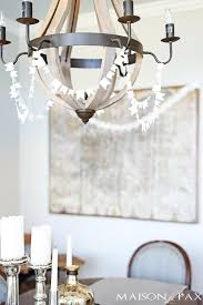 sewn white paper flags dd around a wine barrel chandelier for a festive look