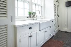 cottage laundry room features white shaker cabinets adorned with oil rubbed bronze hardware topped with white countertop framing a farmhouse sink and deck