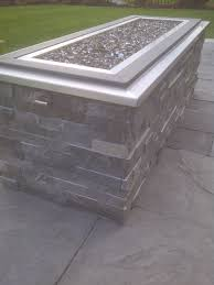 raised gas fire pit with crushed glass stone cladding and stainless steel cap