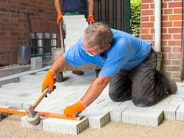 a man lays the patio slabs for his patio to cut the cost