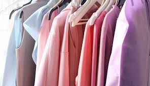 various colored tops in a closet