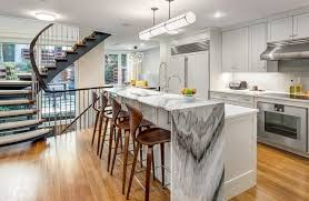 contemporary kitchen with waterfall countertop and calacatta black marble and maple wood flooring