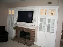 white wall unit with tv over fireplace