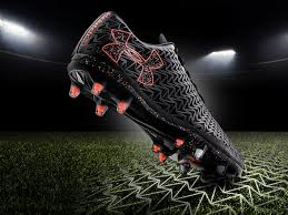under armour football boots. at night, a black and orange ua clutchfit force 3.0 soccer cleat striking grass under armour football boots r