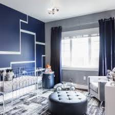 Artistic Nursery With Navy Blue Accent Wall and Clear Crib