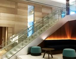 track rail with glass panels sets a minimalist tone that starts in this corporate office lobby transportation glass railing on stairs and balcony