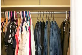 a clean organized closet with jeans hanging on hooks and shirts on hangers