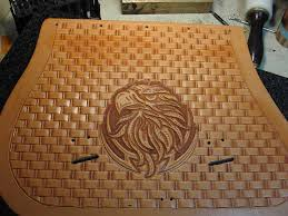 an eagle carved in a lid with the basket weave stamp background before d black