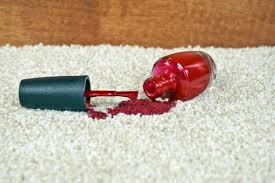 bottle of red nail polish spilling on a beige carpet