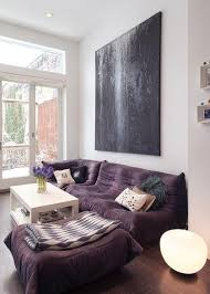 a plush plum sofa looks deep and luxurious and even matches well with a large piece of textured black expressionist art