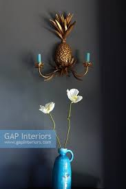 vase of flowers under pineapple wall sconce