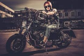 biker and his bobber style motorcycle on a city streets stock
