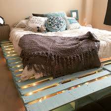 DELICATE PASTEL TURQUOISE PALLET BED FRAME LIT BY STRING LIGHTS