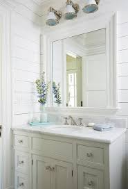coastal style bath lighting. gorgeous white beach style bathroom is fitted with industrial wall sconces mounted to a shiplap coastal bath lighting e
