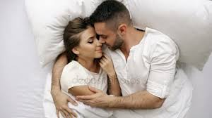 young beautiful and loving couple kiss and hug into bed while waking up in the morning top view of attractive man kissing and talking his smiling wife