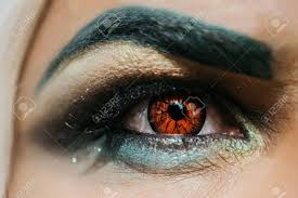 male eye with dark eyeshadow makeup black eyebrow and orange colored decorative contact lens with serious