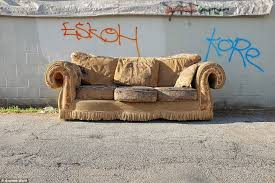 the sofas of la a grubby looking couch lies in front of a wall