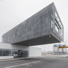 the cantilevered office is covered with remotely adjustable metal gratings