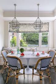bright breakfast nook with bistro chairs and window seat designed by grant k gibson featuring