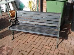attractive wooden garden bench with wrought iron arms
