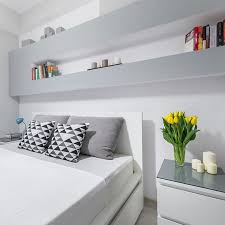 here we have another modern styled room the colors are very neutral and bright the shelving above the bed is perfect for storing valuables and anything