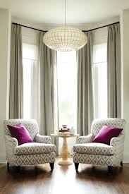 BEAUTIFUL bay window treatment: How to make the room look bigger: Living  room, two armchairs, large chandelier, tall windows, drapes hung really  high.