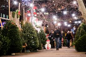 People walk through the SoHo Trees holiday shop at SoHo Square in  Manhattan, New York