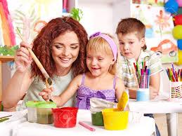 Nursery Teacher Children With Teacher Painting At Easel In School Stock Photo