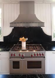 curved black soapstone cooktop backsplash with studded kitchen hood