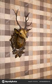 plastic deer head mounted imitation wood wallpaper side view stock photo