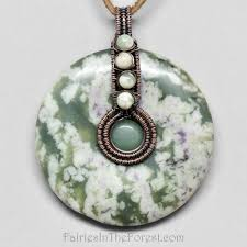 copper wire wrapped peace jade donut pendant on a brown leather necklace