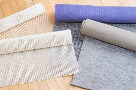 several rolls of rug pad material slightly unrolled atop a wooden floor