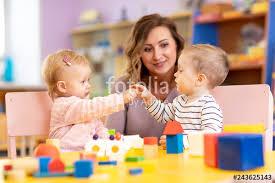 Nursery Teacher Nursery Teacher Looking After Children In Nursery Little Kids