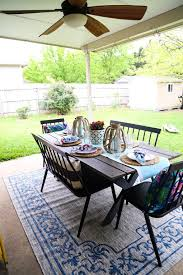 back patio with a table two benches and two chairs