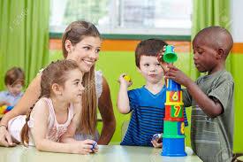 Nursery Teacher Children With Nursery Teacher Building Tower In A Kindergarten