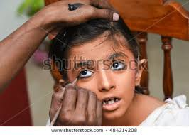 makeup artist applies eye shadow for young indian women kid child wearing